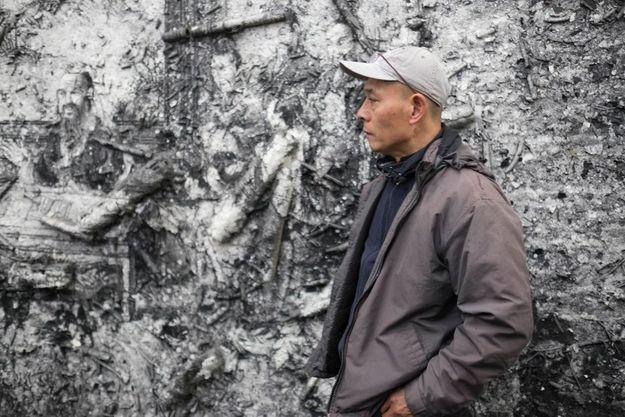 Zhang Huan devant l'un de ses toiles
