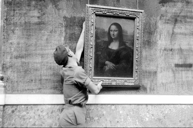 """Un employé du musée accroche le célèbre portrait de Mona Lisa plus connu sous le nom de """"La Joconde"""", peinture de Léonard de Vinci (1452-1519), le 6 octobre 1947, lors de la réouverture de la grande galerie du musée du Louvre."""