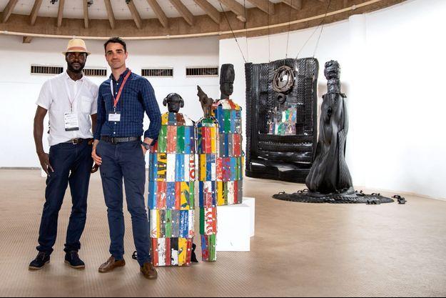 Nyaba Léon Ouedraogo et Christophe Person posent devant une oeuvre de Xenson.