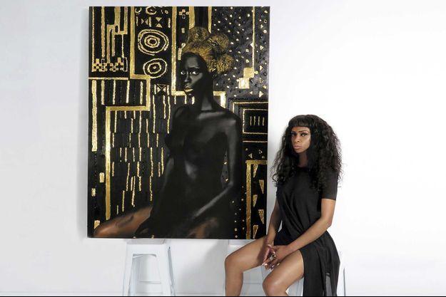 Lina Iris Viktor dans son studio new-yorkais en 2014, elle pose devant son œuvre.