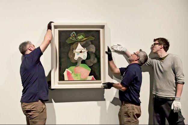 Les équipes techniques du Centre Pompidou installent « Le chapeau à fleurs » de Pablo Picasso.