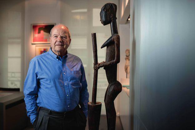 Dans son bureau, Marc Ladreit de Lacharrière pose devant une sculpture dogon.