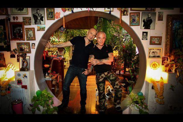 Gilles et Pierre, chez eux, dans leur salon. Un véritable musée pop où Goldorak côtoie Bob l'Eponge et des divinités orientales.