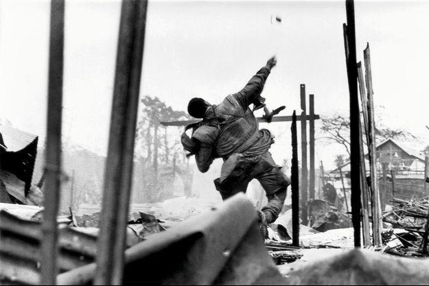 Vietnam, février 1968. Marine américain lançant une grenade pendant la bataille de Hué.