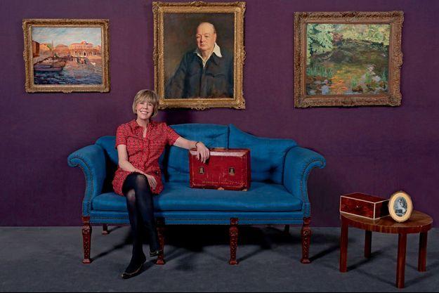 Dans les salons de Sotheby's à Londres. A côté d'Emma, la mallette de chancelier de l'Echiquier (1924-1929) de Winston Churchill. Derrière elle, deux œuvres de son grand-père, « Le port », Cannes 1933, « Bassin aux poissons rouges », Chartwell 1932, et au centre son portrait par Oswald Birley en 1950. Sur la table basse, une de ses boîtes à cigares et sa photo à 5 ans.