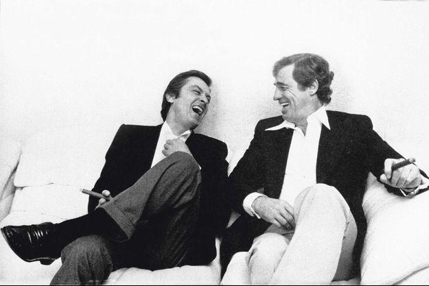 1982. Pour Paris Match, Alain Delon se rend chez Jean-Paul Belmondo. Les deux acteurs commentent, dans la bonne humeur, un sondage où le premier est perçu comme l'homme le plus séduisant (58 % des Français) tandis que le second est le plus populaire pour un déjeuner en tête à tête (48 %).