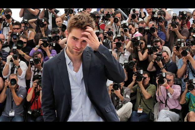 Robert Pattinson joue le timide devant les photographes.