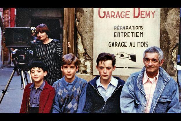 Demy devant le garage familial sur le tournage de « Jacquot de Nantes », avec à ses côtés les acteurs qui interprètentsonrôle à différents âgeset Agnès en arrière-plan.