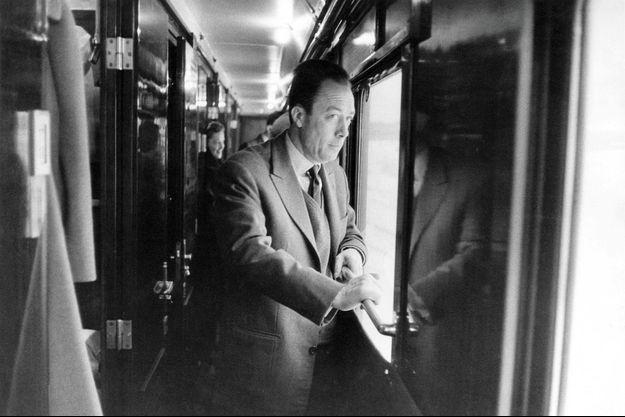 Albert Camus, prix Nobel de littérature en 1957 pour l'ensemble de son oeuvre, part en Suède en train pour recevoir le prix : attitude de l'écrivain debout dans un couloir, regardant par une vitre.