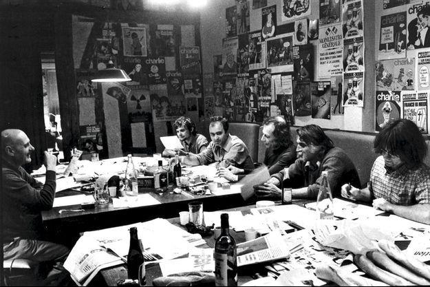 Fin de bouclage : ils travaillent, cassent la croûte, carburent à l'humour mais pas seulement… avec, de gauche à droite, Choron, Reiser, Wolinski, Gébé, Cavanna et Cabu, en 1979.