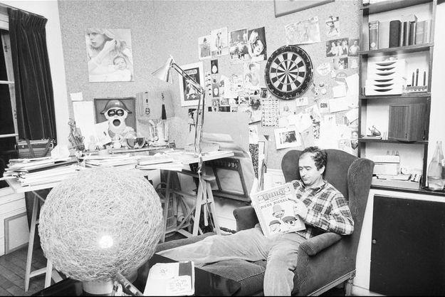 Georges Wolinski, chez lui, lisant un album des Pieds Nickelés.
