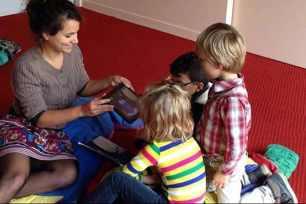 Léna Mazilu jouant avec des enfants en lisant le livre numérique «Chouette».