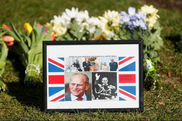 Un cadre et des fleurs déposés en mémoire du prince Philip, devant le palais de Windsor.