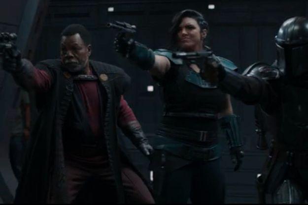 """A gauche de l'écran, un homme portant un jean et un t-shirt est visible durant cette scène de combat de """"The Mandalorian""""."""
