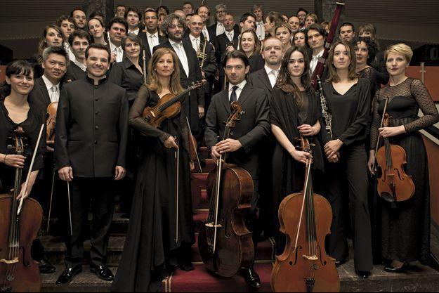 Anne Gravoin, entre Lionel Bringuier (à g.) et le violoncelliste Gautier Capuçon, soliste invité, devant les 48 musiciens de l'Alma Chamber Orchestra.