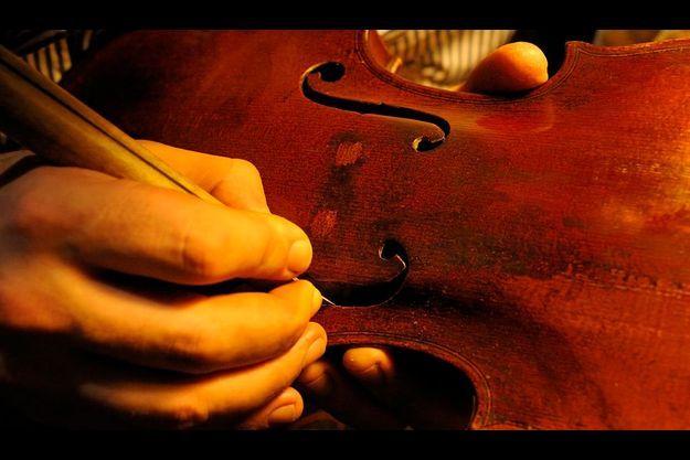 Au 45 rue de Rome à Paris, le quartier où se concentre l'univers de la musique. Martin, 27 ans, compagnon luthier, nettoie les ouïes de la table d'harmonie d'un violon en restauration.