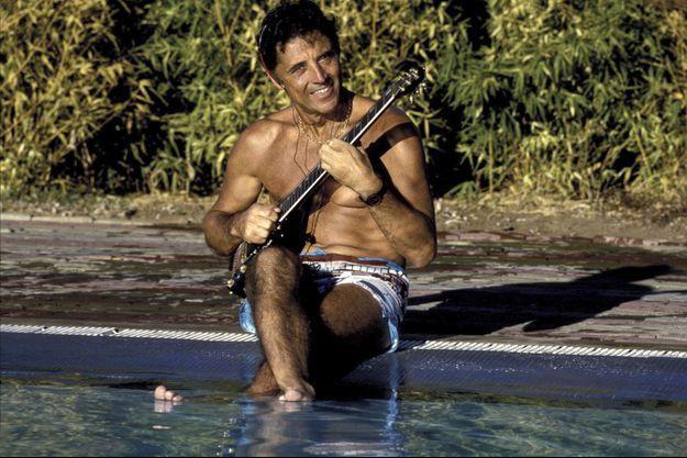 Sacha Distel en vacances au cap d'Agde dans le complexe sportif de Pierre Barthes : le chanteur jouant de la guitare, un écouteur sur les oreilles, en maillot de bain, assis au bord d''une piscine, les pieds dans l''eau.