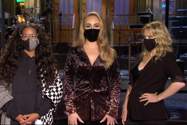 """Adele entre la chanteuse Gabriella Wilson (dite H.E.R.) et Kate McKinnon dans le """"Saturday Night Live"""""""