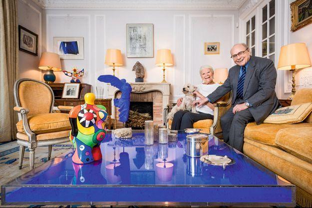 Alain Pompidou et sa femme, Nicole, avec leur chienne Daisy, à Paris. Aux murs, de g. à dr., des œuvres de Fautrier, Hartung, Viera da Silva, de Staël et La Fresnaye. Sur le secrétaire, une photo de De Gaulle et Pompidou en 1962. Sculptures de Niki de Saint Phalle et d'Yves Klein (en bleu).