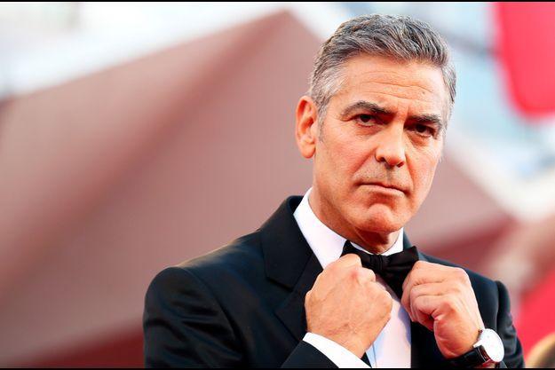 """George Clooney réajuste son noeud-papillon lors de la présentation de """"Gravity"""", au Festival de Venise en 2013. On le retrouvera à l'affiche de """"The Monuments Men"""", qu'il a réalisé le 12 mars prochain."""