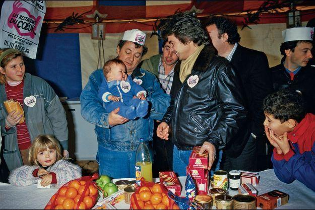 Sous le chapiteau de Gennevilliers, le 22 décembre 1985, Coluche accueille le premier bébé – déjà badgé – sous le regard attendri de Daniel Guichard
