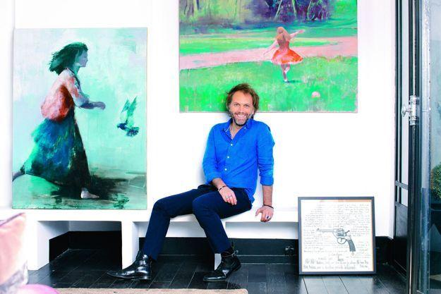 Dans le couloir qui mène à son bureau, deux tableaux signés Philippe Vasseur. Celui de droite a été commandé spécialement pour le film. A Paris, le 20 mars 2021.