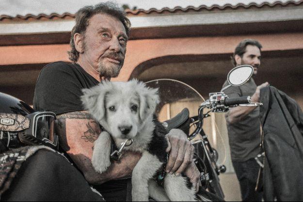 Dans ses bras, Cheyenne, une petite chienne recueillie sur la route. Derrière, Sébastien Farran.