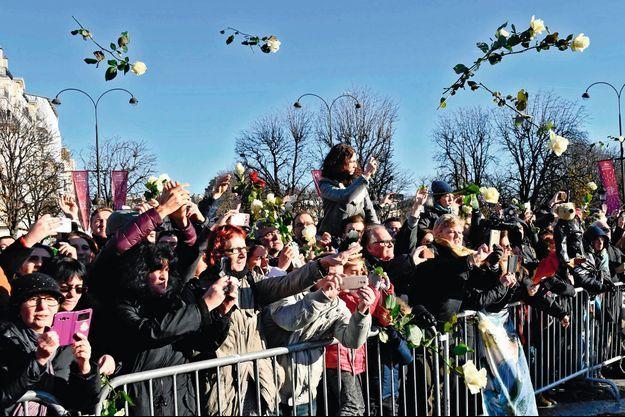 Les fans font pleuvoir une pluie de roses blanches alors que la dépouille quitte la place de la Madeleine.