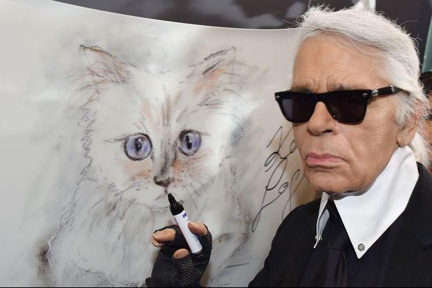 Karl Lagerfeld devant un dessin de sa chatte Choupette.