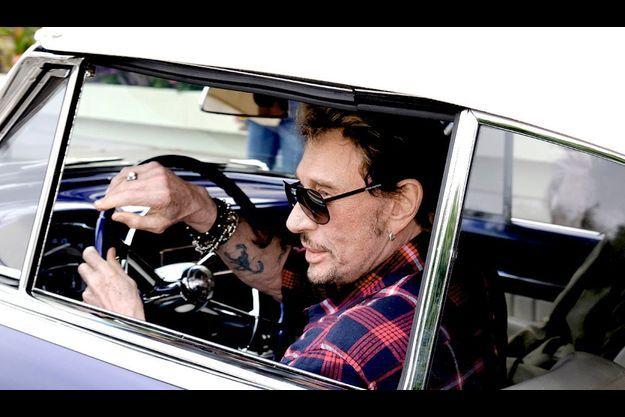 Johnny Hallyday au volant d'une Cadillac, à Pacific Palisades, en Californie.