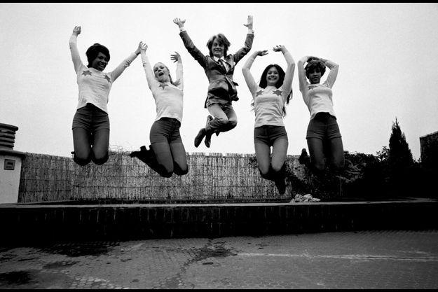 En France, à Paris, le 29 novembre 1971, Claude FRANCOIS, chanteur, au milieu des Clodettes, sautant, sur le toit de son siège social.