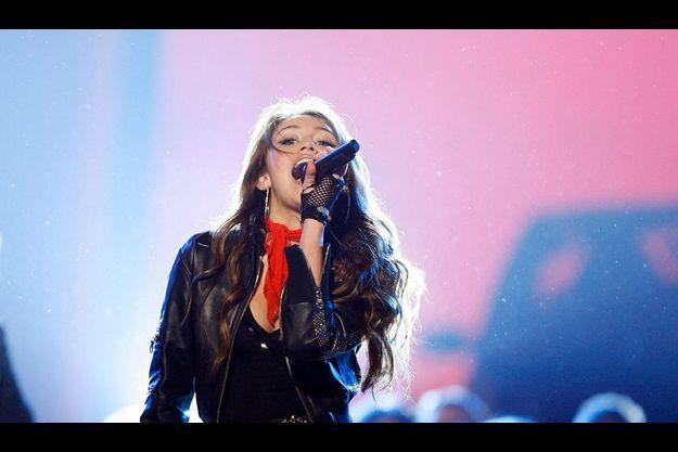 Tenue décontractée, regard provocateur, Miley Cyrus dévoile, sur haut-parleur, une féminité savamment mise en scène.