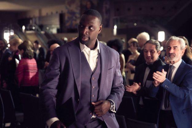 Omar Sy est Arsène Lupin, ici déguisé en millionnaire lors d'une vente aux enchères.