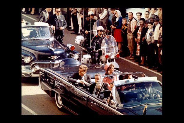22 novelbre 1963, Jackie et JFK arrivent à Dallas. Ils montent dans la Lincoln derrière le gouverneur Connally et son épouse. Le garde du corps Clint Hill (lunettes noires et pochette blanche) se tient à l'arrière de la Lincoln.