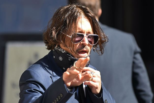 Johnny Depp, à demi-masqué le temps d'un instant, s'apprête à faire son entrée dans la Haute cour de Londres, le 7 juillet.