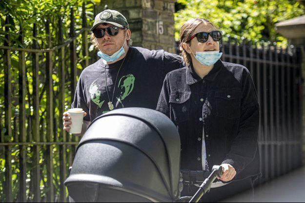 Rupert Grint en balade avec sa compagne Georgia Groome et leur fillette en mai 2020 à Londres, quelques jours après la naissance du bébé