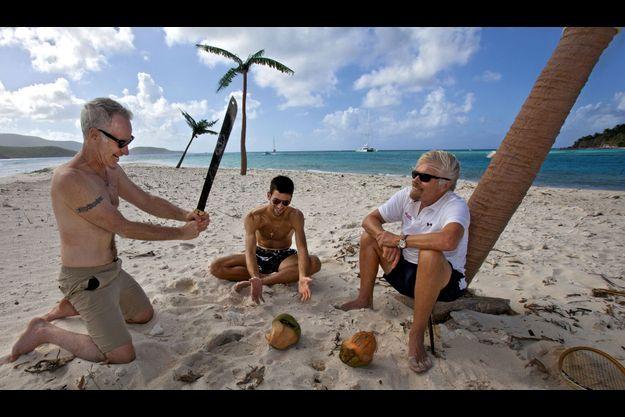 Cool attitude. De g. à dr., John McEnroe tente d'ouvrir une noix de coco à la machette, Novak Djokovic, le n° 1 mondial du tennis, et Richard Branson. Derrière, les palmiers sont en plastique. Branson n'a jamais réussi à faire pousser ces arbres sur son île.