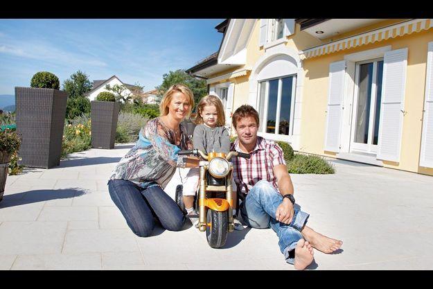 Sur la terrasse de leur maison en Suisse, avec Séverine, sa femme, et leur fille, Valentine, bientôt 3 ans. Les petites voitures et motos à pédales sont bien sûr ses jouets préférés.