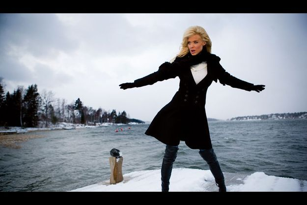 Sur le ponton de la nouvelle maison familiale, elle se joue du blizzard, sculpturale en cuissardes et redingote noires.
