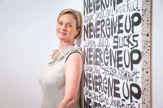 """Delphine Boël devant l'une de ses oeuvres où l'on peut lire """"never give up"""", n'abandonne jamais."""