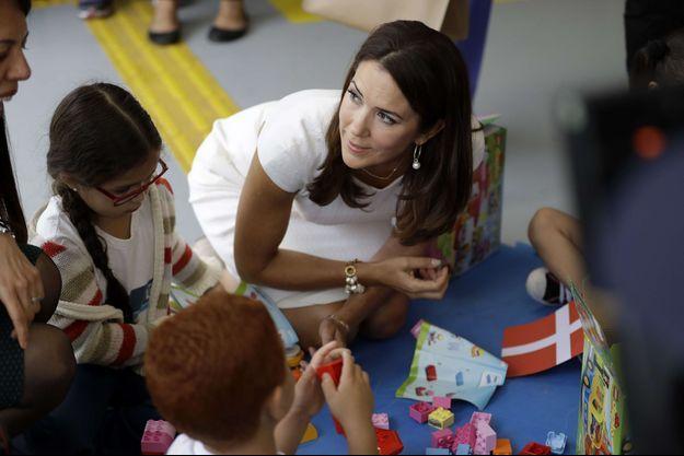 La princesse Mary de Danemark avec des enfants d'un bidonville de Rio de Janeiro auxquels elle a donné des Lego, le 3 août 2016