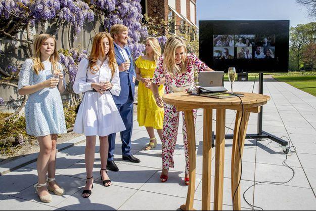 Le roi Willem-Alexander des Pays-Bas à La Haye, le 27 avril 2020, avec la reine Maxima et leurs filles ainsi que sa mère l'ex-reine Beatrix et d'autres membres de la famille royale en vidéo