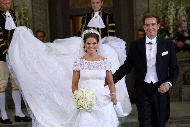 Pas de demoiselles d'honneur mais deux valets pour porter la traîne de 4 mètres de longueur de la princesse Madeleine. Chris arbore la croix de l'Ordre royal de l'étoile Polaire.