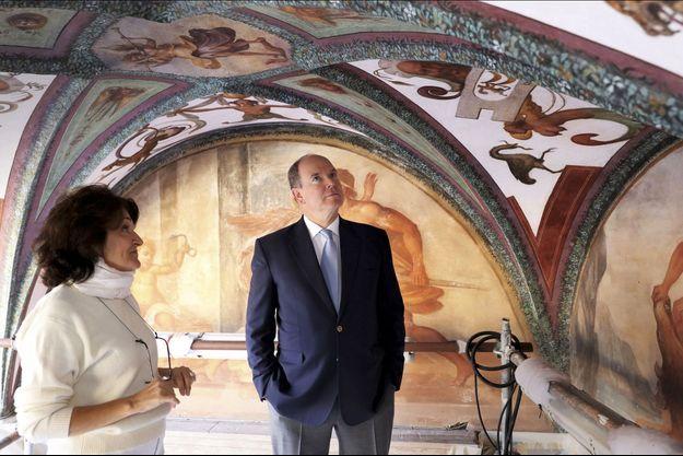 Le prince et Laurence Guilhemsans, responsable des opérations de réintégration picturale, devant les peintures restaurées de la galerie d'Hercule.