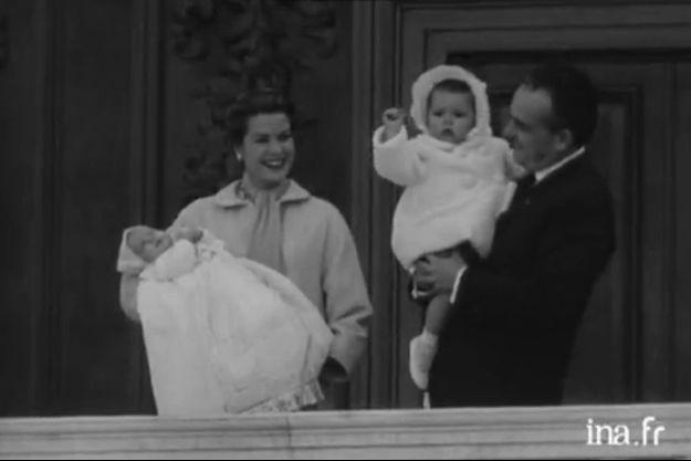 Le prince Albert de Monaco, dans les bras de son père Rainier, en avril 1958. A côté, sa mère la princesse Grace tient dans ses bras la petite Caroline.