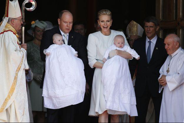 Le Prince Albert II et la Princesse Charlène de Monaco tiennent leurs enfants, le Prince Héréditaire Jacques et la Princesse Gabriella, à la sortie de leur baptême.