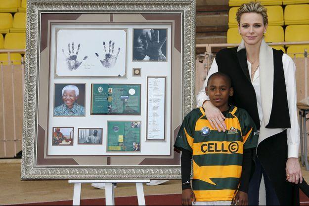 Le 11 avril, au stade Louis-II de Monaco. Dans les bras de Charlène, Kelvin, 12 ans, jeune pousse de rugbyman venue des townships de Johannesburg.