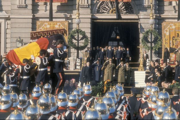Les obsèques nationales du général Franco à Madrid, le 23 novembre 1975 : l'arrivée du cercueil du caudillo pour la cérémonie, place de l'Orient. Au centre sur les marches, son successeur Juan Carlos Ier. A l'arrière-plan à droite, sa veuve, Dona Carmen.