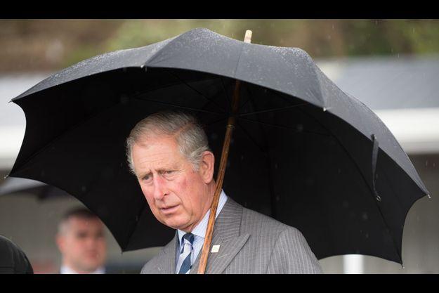 Le prince Charles, avec un parapluie, à Auckland.