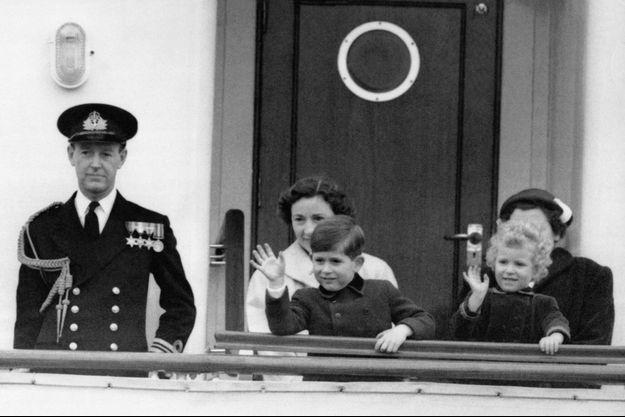 Le prince Charles et sa petite soeur la princesse Anne à bord du Britannia le 14 avril 1954 à Portsmouth, saluant la foule avant leur départ pour Tobrouk